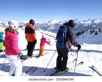 Skiers enjoy the view of winter mountains in the Portes du Soleil near Morgins, Switzerland