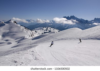 Skiers in French Alps carve turns as they make their way down a piste in Avoriaz, Portes du Soleil ski area. Swiss Alps can be seen in background