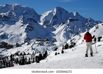 Skiers in front of Marmolada and Gran Vernel group on Italian Dolomites. Italy.