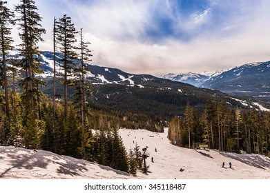 Skiers go down the ski slopes with the Canadian Rocky Mountains in the background on a bright sunny day.
