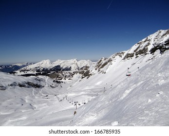 Skiers on high alpine piste  with chairlift  in valley above  Avoriaz, France