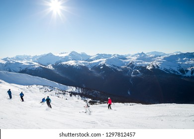 Skiers on a hill at the top of Blackcomb, 7th Heaven, with a view looking toward Whistler on a sunny day.
