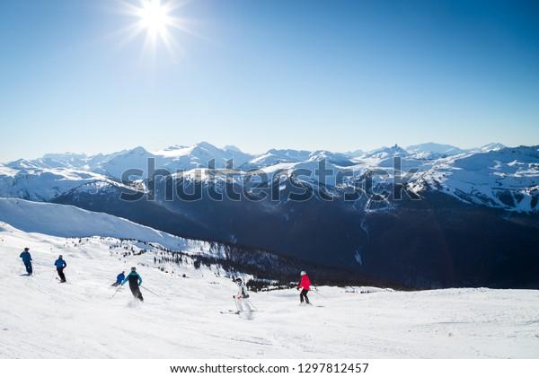 ブラックコームの頂上にある丘の上のスキーヤーたち、晴れた日にウイスラーを見る景色。