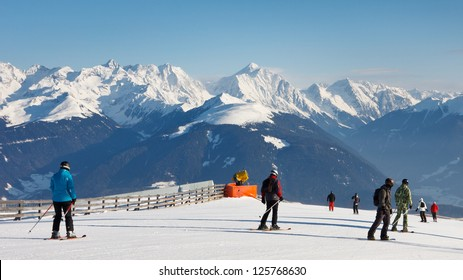 Skiers on a ski run in the Dolomites, South Tyrol, on a beautiful winter day.