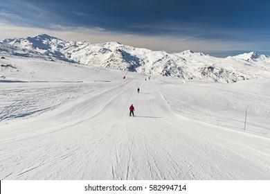 Skiers on a ski slope piste in winter alpine mountain resort
