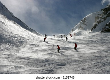 Skiers on Swiss Alps slopes. Snow blown by the wind gives a mysterious feel to the scene.