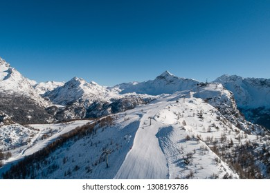 Skiers on the track, ski station in Valtellina. Panoramic view from a drone