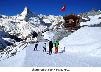 Skiers on the way to ski slope in Swiss Alps in sunny day, Matterhorn behind. Small wooden house with red swiss flag near by ski slope. Mountains and skiing resort photo manipulation, Switzerland.