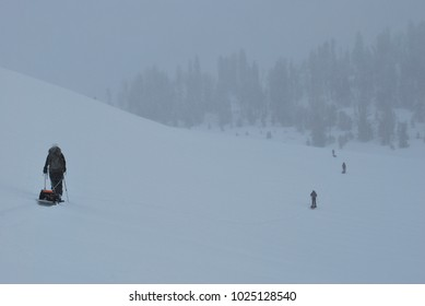 Skiers pulling sleds on a 16 day backcountry expedition in the Absaroka mountains of Wyoming during a snow storm.