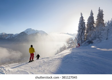 Skiers set off down a piste in the Morzine resort, part of the Portes du Soleil ski area in France. A snow lance can be seen spraying snow from the side of the run.