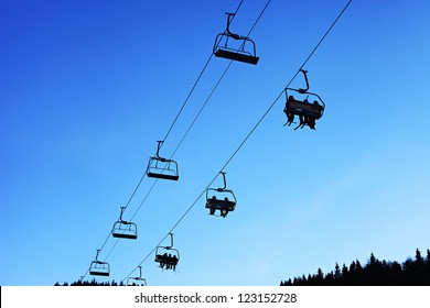Skiers silhouettes on lift over blue sky.