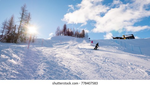 Skiers skiing downhill on mountain sunny landscape at Sauze D'Oulx piedmont italy