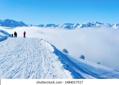 Skiers skiing in Zillertal Arena ski resort in clouds in Tyrol in Mayrhofen in Austria in winter Alps. Alpine mountains with white snow and blue sky. Downhill peaks at Austrian snowy slopes.