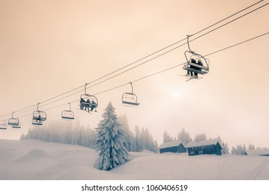 Skiers and Snow Boarders travelling on a chair lift at Morzine Ski Resort in France.
