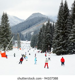 Skiers and snowboarders going down the slope at Jasna ski resort in Slovakia