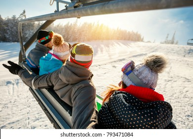 skiers and snowboarders on ski lift in the mountain at winter vacations back view