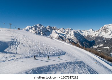 Skiers and snowboarders on the track, ski station in the Italian Alps. Valtellina.