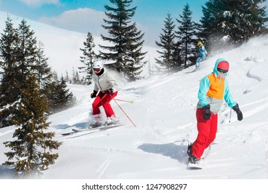 Skiers and snowboarders riding on a ski resort on snowy winter mountain with fir-tree background scenic view. Blue sky