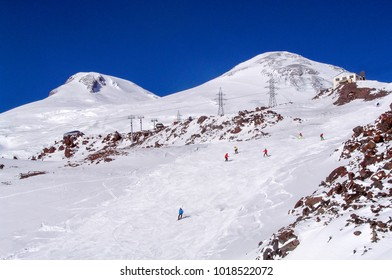 Skiers, snowboarders, skate at the top of a snowy mountain. A view of the tops of Elbrus. Elbrus, Europe, Russia, the Caucasus, Kabardino-Balkaria, Karachay-Cherkessia. High-voltage poles.