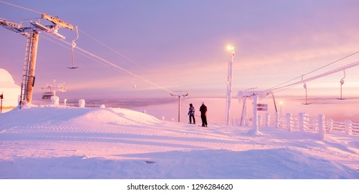 Skiers stand on top of the mountain and watch the sunrise. Early morning. Panorama. athletes and lifts in the sun. Kuusamo Ruka. Finland Lapland. - Shutterstock ID 1296284620