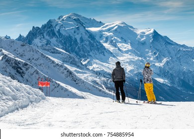 Skiers standing on a ski slope looking across to Mont Blanc in winter.  The male and female are wearing bright ski clothes.