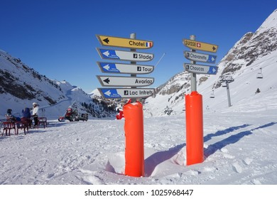 Skiers taking a break by direction signs on the piste above the ski resort of Avoriaz in the French Alps.