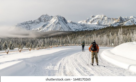 Skiers travel on a snow covered road to get into the mountains