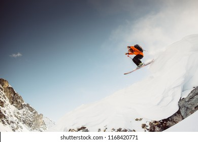 Skiier in the alps jumping down cliff in red jacket with blue sky and sunny weather