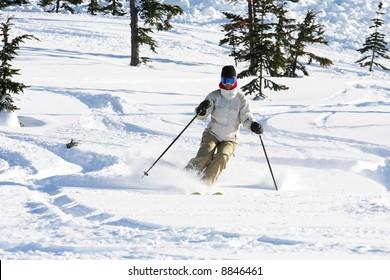 A skiier enjoying fresh snow in Whistler, BC.