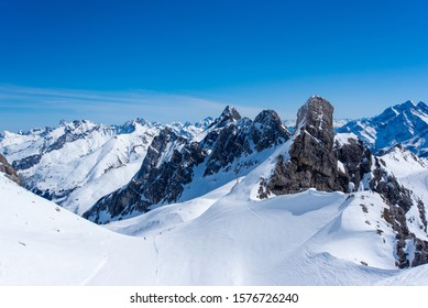 Skiing amidst the rocky mountain peaks in the Austrian Alps under a clear blue sky.