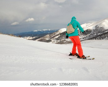 Skiing with backpack in Bakuriani with snow capped mountain in the background