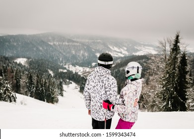 Skiing. Couple skiing in the snowy mountains. Man and woman in ski mask on skis on snow in Carpathian. On background of forest and ski slopes. Winter nature.