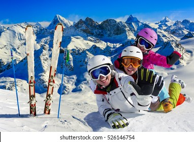 Skiing family enjoying winter vacation on snow in sunny cold day in mountains and fun. Switzerland, Alps.