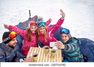 Skiing family laughing and enjoying in winter vacation on snow and making selfie