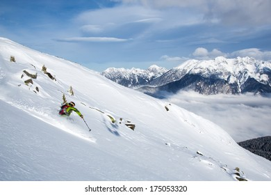 Skiing fresh powder turns above the cloud inversion in the mountains of the Tyrolean Alps in Austria.