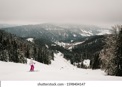 Skiing. Good skiing in the snowy mountains. Woman in ski mask on skis on snow in Carpathian. On background of forest and ski slopes. Winter nature. Nice winter day.