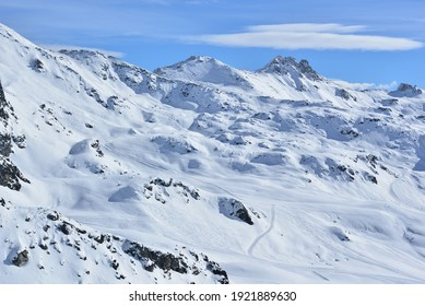Skiing in the high mountains with tracks in the fresh snow in the Val d'Anniviers, in the swiss alps