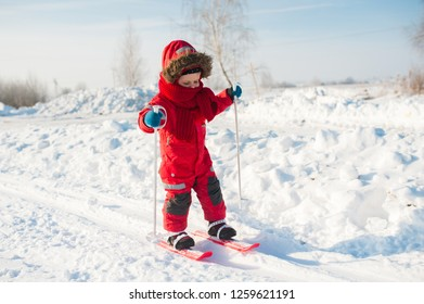 Skiing  little skier portrait. Red winter overalls. Girl with ski poles
