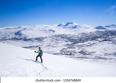 Skiing Man having fun doing active sports, enjoying the view of the beautiful landscape of Sweden. Valley of Storulvån from mountain Getryggen Åre kommun.