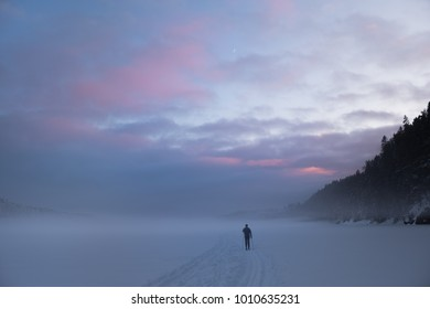 Skiing on a frozen, misty lake. New moon behind coloured evening skies.  Forests in Oslo