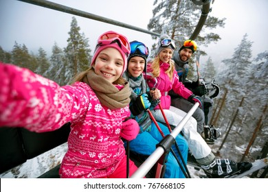 Skiing, ski lift, ski resort - happy smiling family skiers on ski lift making selfie