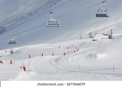 Skiing slope in the French Alpes, with skilift overhead, falling snow int hte air