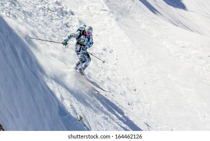 Skiing in the sunlight at high speed on an extremely steep slope