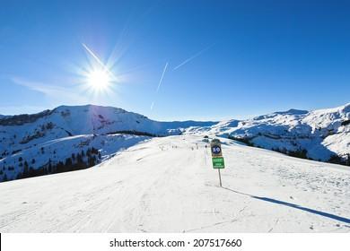 skiing tracks on snow slopes of mountains in sunny day in Portes du Soleil region, Morzine - Avoriaz, France