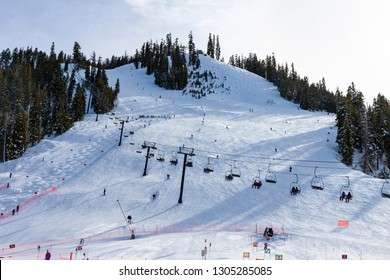 Skiing at a Valley resort on the banks of the Truckee River in Placer County, California. People in cahir lift, downhill sking and sking a mogul run.