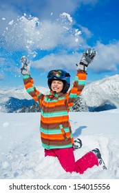 Skiing, winter, teenage girl - young skier girl playing in snow in winter resort