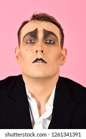 Skill at improvisation. Mime artist. Mime with face paint. Man with mime makeup. Theatre actor miming. Stage actor miming. Theatrical performance art and pantomime. Comedian or tragedian performer.