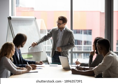 Skilled 30s caucasian leader in eyeglasses coaching interested business people, giving educational workshop presentation in office. Concentrated employees listening to professional coach at workshop. - Shutterstock ID 1896357391