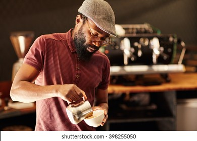 Skilled African barista pouring frothed milk into a cappucino