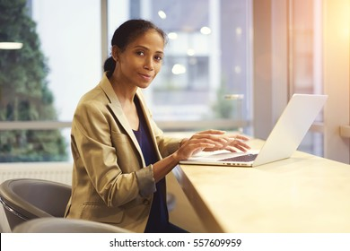 Skilled afro american female administrative typing message on keyboard of laptop computer having online conversation with colleagues using wifi connection sitting at desktop in modern office